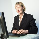 Businesswoman typing. Caucasian businesswoman typing on computer keyboard smiling royalty free stock photo