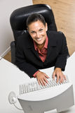 Businesswoman typing on computer. Businesswoman smiling at the camera while working at her computer Royalty Free Stock Images