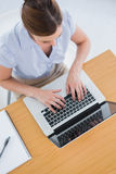Businesswoman typing on her laptop overhead. At desk in office Stock Images