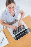 Businesswoman typing on her laptop and smiling up at camera. Businesswoman typing on her laptop at desk and smiling up at camera in an office Royalty Free Stock Image