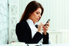 Businesswoman typing on her smartphone Royalty Free Stock Image