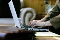 Businesswoman Typing in Hotel Atrium Stock Photography