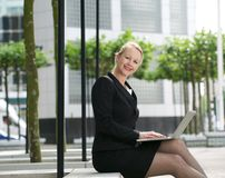 Businesswoman typing on laptop outdoors Stock Photos