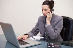 Businesswoman typing on laptop while talking on the phone Royalty Free Stock Image
