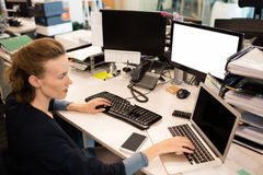 Businesswoman typing on laptop while using desktop pc Royalty Free Stock Photo