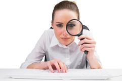 Businesswoman typing and looking through magnifying glass Royalty Free Stock Image