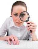 Businesswoman typing and looking through magnifying glass Royalty Free Stock Photos