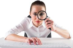 Businesswoman typing and looking through magnifying glass Stock Photo
