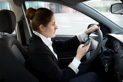 Businesswoman typing message while driving a car Royalty Free Stock Photos