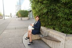 Businesswoman typing message and listening to music outside with. Businesswoman listening to music and chatting with smartphone and in ear phones outside Royalty Free Stock Image
