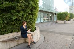 Businesswoman typing message and listening to music outside with. Businesswoman listening to music and chatting with smartphone and in ear phones outside Stock Images