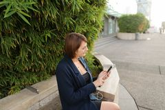 Businesswoman typing message and listening to music outside with. Businesswoman listening to music and chatting with smartphone and in ear phones outside Royalty Free Stock Photos