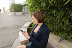 Businesswoman typing message and listening to music outside with. Businesswoman listening to music and chatting with smartphone and in ear phones outside Royalty Free Stock Photography