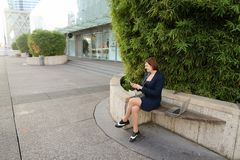 Businesswoman typing message and listening to music outside with. Businesswoman listening to music and chatting with smartphone and in ear phones outside Stock Photo
