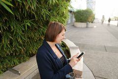 Businesswoman typing message and listening to music outside with. Businesswoman listening to music and chatting with smartphone and in ear phones outside Stock Photos