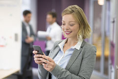 Businesswoman typing a message on smart-phone in modern office Royalty Free Stock Photos