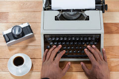Businesswoman typing on typewriter with vintage camera, telephone and mobile phone. Hand of businesswoman typing on typewriter with vintage camera, telephone and Stock Images