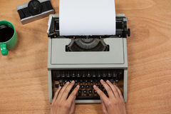 Businesswoman typing on typewriter with vintage camera, telephone and mobile phone. Hand of businesswoman typing on typewriter with vintage camera, telephone and Royalty Free Stock Photos