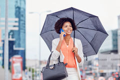 Businesswoman with umbrella calling on smartphone Royalty Free Stock Photos