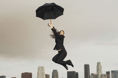 Businesswoman With An Umbrella Flying Above City Stock Photos