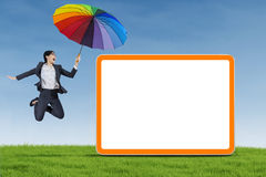 Businesswoman with umbrella jumping on the meadow Royalty Free Stock Image