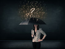 Businesswoman with umbrella and a lot of drawn question marks Royalty Free Stock Image