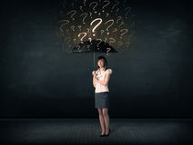 Businesswoman with umbrella and a lot of drawn question marks Stock Image