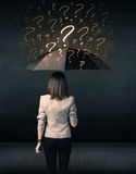 Businesswoman with umbrella and a lot of drawn question marks Royalty Free Stock Photos