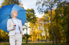Businesswoman with umbrella over autumn background Royalty Free Stock Image
