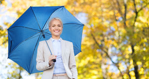 Businesswoman with umbrella over autumn background Royalty Free Stock Photo