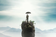 Businesswoman with umbrella on the peak Royalty Free Stock Photography