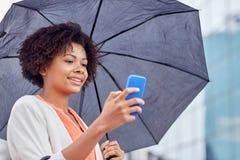 Businesswoman with umbrella texting on smartphone Stock Photo