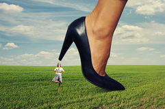 Businesswoman under big heel at outdoor Stock Photos