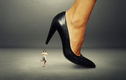 Businesswoman under big heel over dark Stock Images