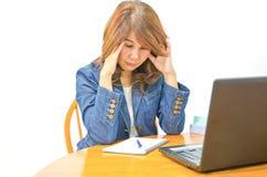 Businesswoman under stress sitting at desk Stock Photo
