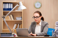 The businesswoman under stress from too much work in the office Stock Photos
