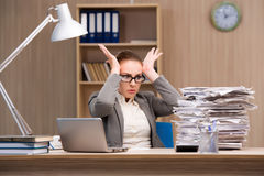 The businesswoman under stress from too much work in the office. Businesswoman under stress from too much work in the office Stock Photography