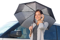 Businesswoman under umbrella by luxury car calling Royalty Free Stock Images