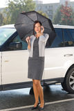 Businesswoman under umbrella by luxury car calling Stock Image