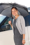 Businesswoman under umbrella by luxury car posing Royalty Free Stock Image