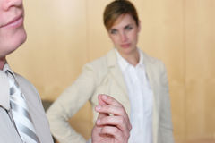 Businesswoman upset. Side view of  businessman rubbing his fingers with woman looking at him Royalty Free Stock Image
