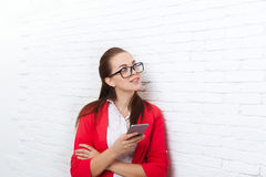 Businesswoman use cell smart phone look up to copy space wear red jacket glasses happy smile Royalty Free Stock Photography