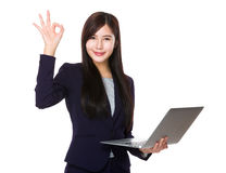 Businesswoman use of laptop and ok sign Stock Images