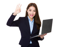 Businesswoman use of the notebook computer and ok sign Stock Images