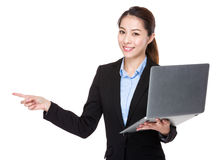 Businesswoman use of notebook and ffinger point aside Royalty Free Stock Image