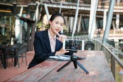 Businesswoman use smartphone for online live streaming. woman re. Asian businesswoman use smartphone for online live streaming. woman recording video blog Royalty Free Stock Photo