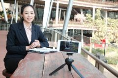 Businesswoman use smartphone for online live streaming. woman re. Asian businesswoman use smartphone for online live streaming. woman recording video blog Royalty Free Stock Photos