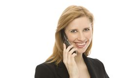 Businesswoman uses cell phone. A businesswoman in a suit uses a cell phone Royalty Free Stock Images