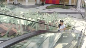 Businesswoman uses cellphone on escalator. Young businesswoman using a cellphone while holding a cup of drink on the escalator in the office lobby stock footage