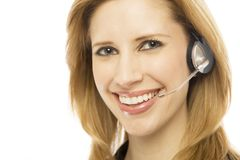 Businesswoman uses headset. Businesswoman in a suit smiles and uses a headset Stock Images